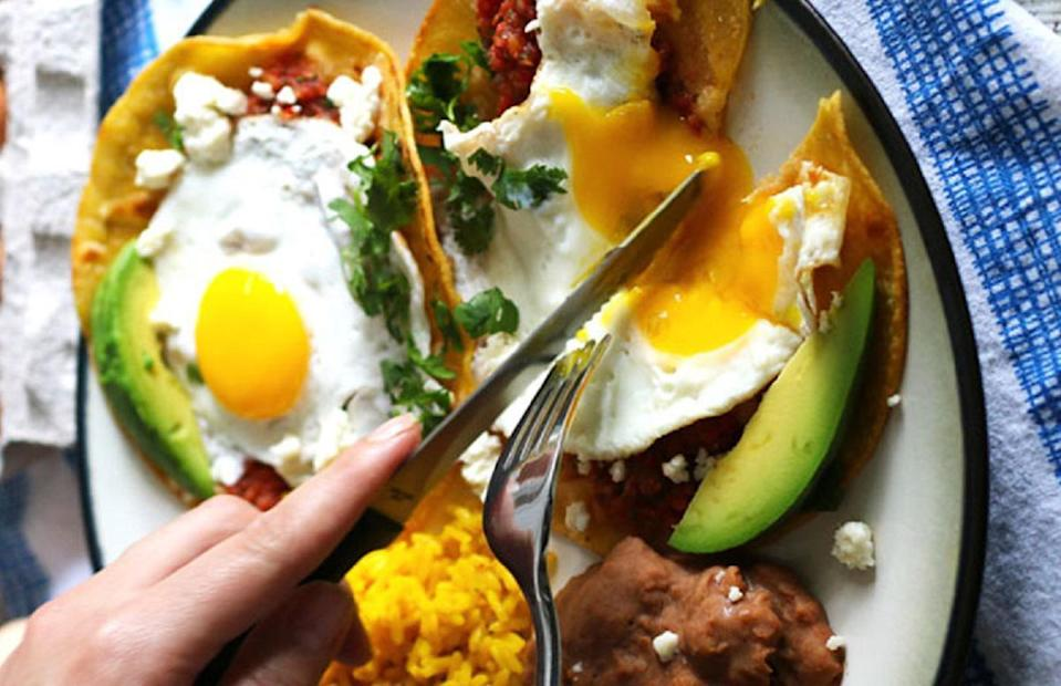 """<p>Like <a href=""""https://www.thedailymeal.com/best-recipes/classic-eggs-benedict?referrer=yahoo&category=beauty_food&include_utm=1&utm_medium=referral&utm_source=yahoo&utm_campaign=feed"""" rel=""""nofollow noopener"""" target=""""_blank"""" data-ylk=""""slk:eggs Benedict"""" class=""""link rapid-noclick-resp"""">eggs Benedict</a>, huevos rancheros is a dish that commonly appears on brunch menus across the country. The yolk from the slightly runny eggs coats the salsa and tortillas and gives the dish a savory, buttery flavor. It's so good that you shouldn't have to wait to go out to get it, add it to your <a href=""""https://www.thedailymeal.com/cook/brunch-recipes-spring-easter-mothers-day?referrer=yahoo&category=beauty_food&include_utm=1&utm_medium=referral&utm_source=yahoo&utm_campaign=feed"""" rel=""""nofollow noopener"""" target=""""_blank"""" data-ylk=""""slk:breakfast rotation"""" class=""""link rapid-noclick-resp"""">breakfast rotation</a> ASAP. </p> <p><strong><a href=""""https://www.thedailymeal.com/recipes/huevos-rancheros-recipe-0?referrer=yahoo&category=beauty_food&include_utm=1&utm_medium=referral&utm_source=yahoo&utm_campaign=feed"""" rel=""""nofollow noopener"""" target=""""_blank"""" data-ylk=""""slk:For the Huevos Rancheros recipe, click here."""" class=""""link rapid-noclick-resp"""">For the Huevos Rancheros recipe, click here.</a></strong></p>"""
