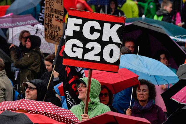 <p>Participants hold placards during a demonstration called by several NGOs ahead of the G20 summit in Hamburg on July 2, 2017. (John MacDougall/AFP/Getty Images) </p>