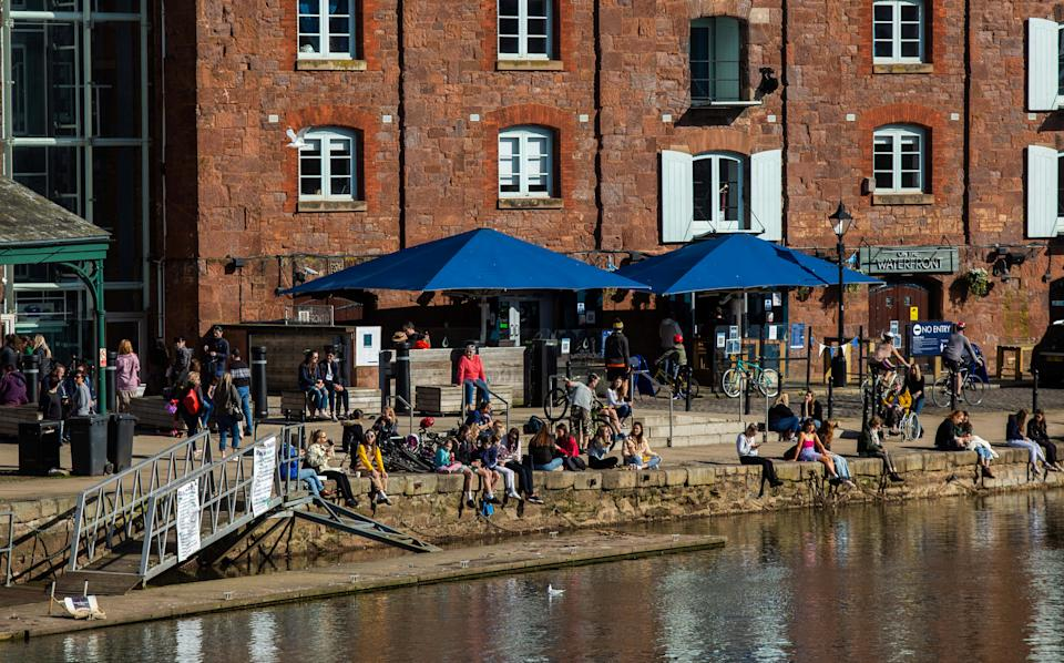 People enjoy the sunshine at the Exeter Quay in Devon. (SWNS)