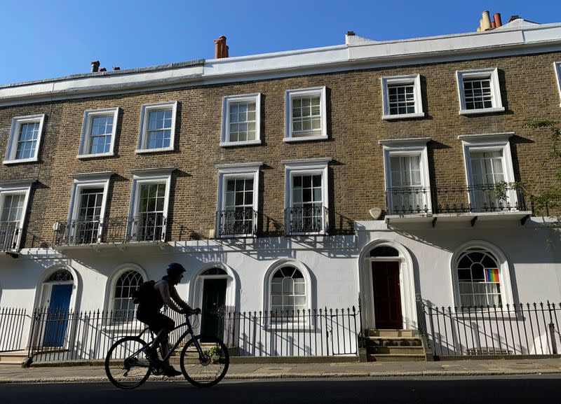 A cyclist rides past houses on a street in Islington, London