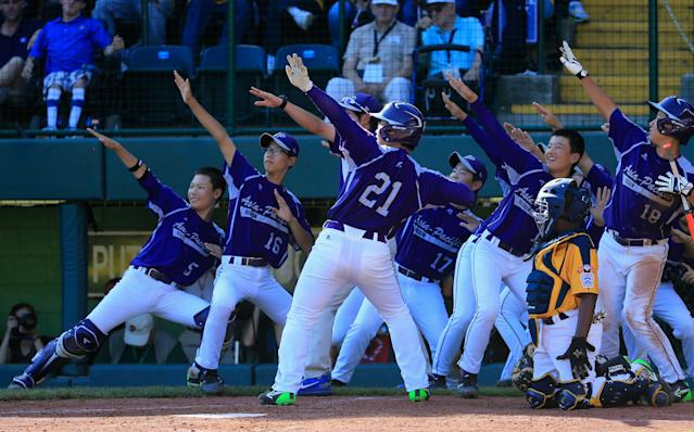 SOUTH WILLIAMSPORT, PA - AUGUST 24: Hae Chan Choi #21 of Team Asia-Pacific celebrates with teammates after hitting a solo home run against the Great Lakes Team from Chicago, Illinois during the sixth inning of the Little League World Series Championship game at Lamade Stadium on August 24, 2014 in South Williamsport, Pennsylvania. (Photo by Rob Carr/Getty Images)