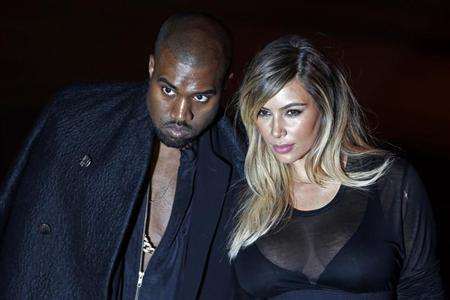U.S. musician Kanye West (L) and companion Kim Kardashian arrive at the Givenchy Spring/Summer 2014 women's ready-to-wear fashion show during Paris Fashion Week September 29, 2013. REUTERS/Charles Platiau