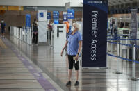 A lone traveler wears a face covering as she stops to check the departure monitors across from the United Airlines ticketing counter in the main terminal of Denver International Airport Tuesday, Aug. 24, 2021, in Denver. Two months after the Sept. 11, 2001 attacks, President George W. Bush signed legislation creating the Transportation Security Administration, a force of federal airport screeners that replaced the private companies that airlines were hiring to handle security. (AP Photo/David Zalubowski)