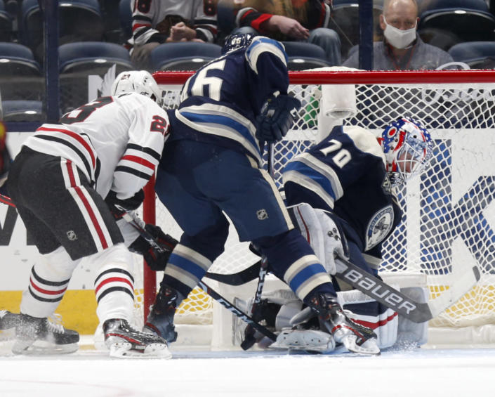 Columbus Blue Jackets goalie Joonas Korpisalo, right, stops a shot in front of teammate defenseman Dean Kukan, center, and Chicago Blackhawks forward Philipp Kurashev during the second period of an NHL hockey game in Columbus, Ohio, Monday, April 12, 2021. (AP Photo/Paul Vernon)