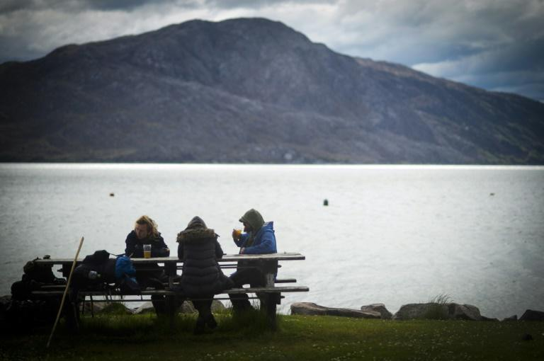 Saying they have fallen out with the owner of the UK's most remote pub locals sit and drink outside The Old Forge, which is up for sale at Inverie in the Scottish Highlands