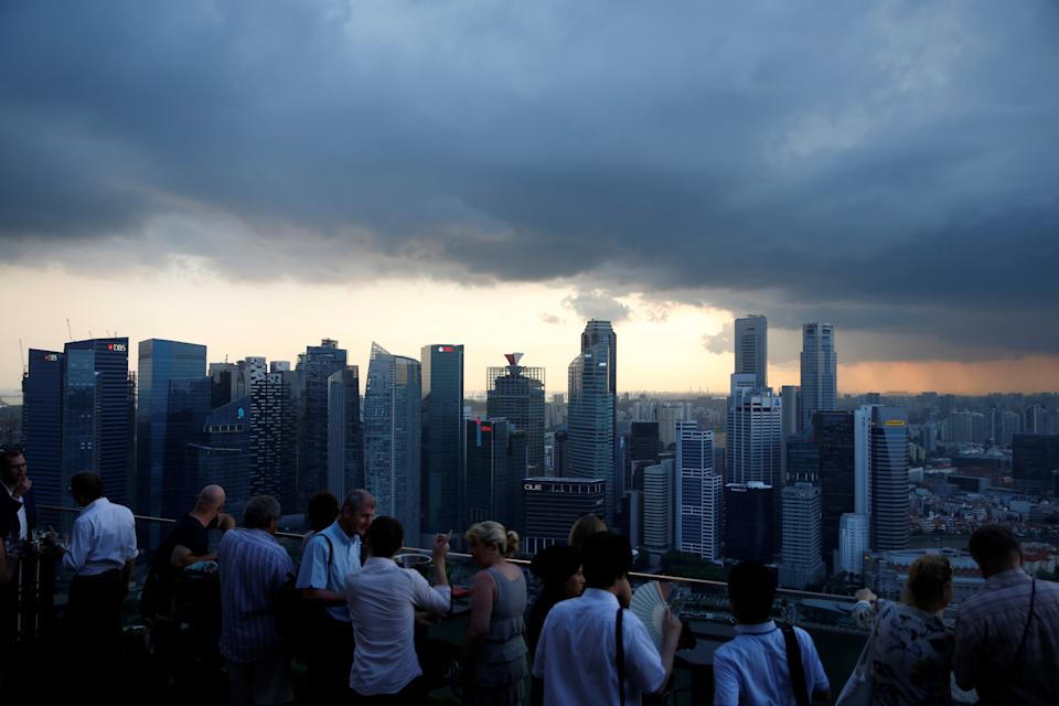 Tourists have drinks at a hotel rooftop bar as clouds gather over the central business district in Singapore June 6, 2016. REUTERS/Edgar Su