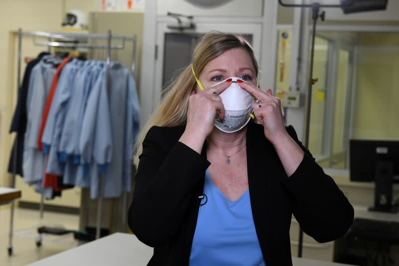 FILE PHOTO: Dr. Nicole McCullough, a global health and safety expert at 3M, demonstrates the correct way to put on a N95 respiratory mask at a laboratory of 3M in Maplewood, Minnesota