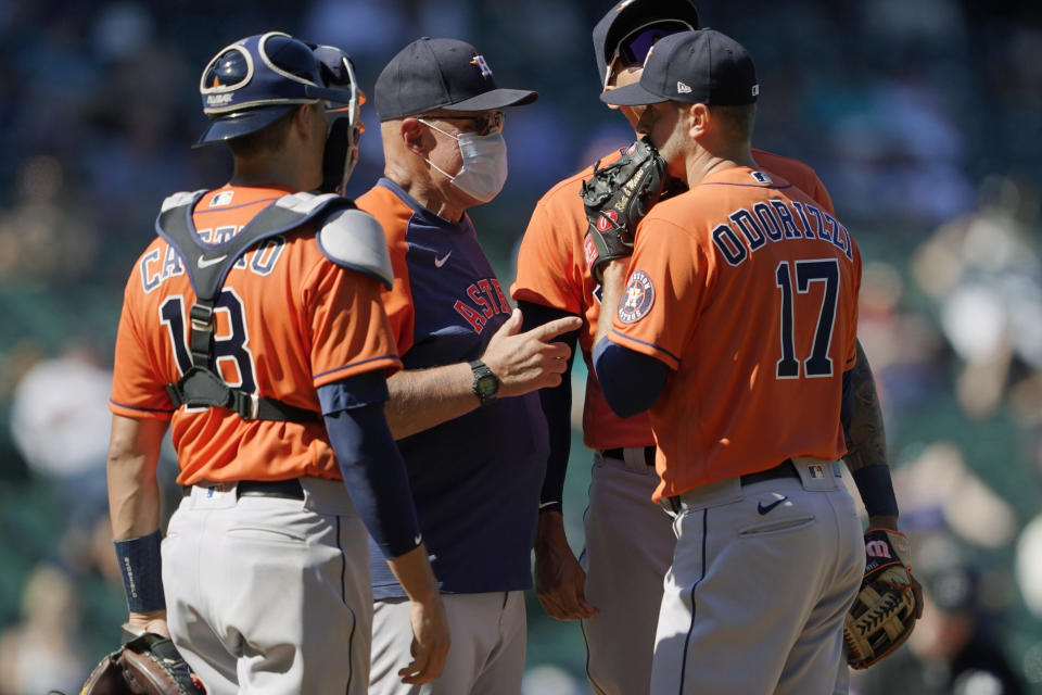Houston Astros starting pitcher Jake Odorizzi (17) talks with pitching coach Brent Strom, second from left, and catcher catcher Jason Castro during a mound conference in the fifth inning of a baseball game against the Seattle Mariners, Sunday, April 18, 2021, in Seattle. (AP Photo/Ted S. Warren)