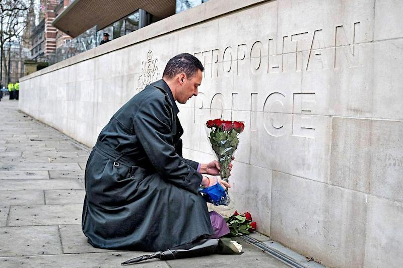 A simple tribute marking Wednesday's attack: a man lays a bunch of flowers outside New Scotland Yard yesterday