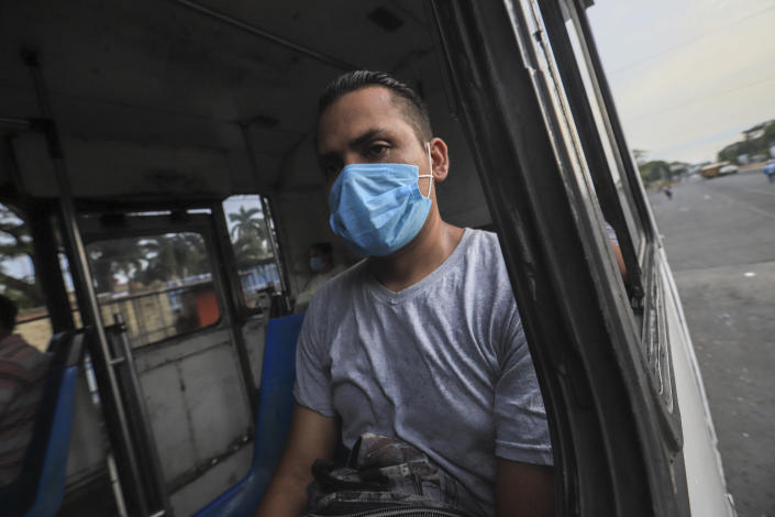 A man wears a mask against the spread of COVID-19 disease, as he rides a bus home in Managua, Nicaragua, Monday, May 11, 2020. President Daniel Ortega's government has stood out for its refusal to impose measures to halt the new coronavirus for more than two months since the disease was first diagnosed in Nicaragua. Now, doctors and family members of apparent victims say, the government has gone from denying the disease's presence in the country to actively trying to conceal its spread. (AP Photo/Alfredo Zuniga)