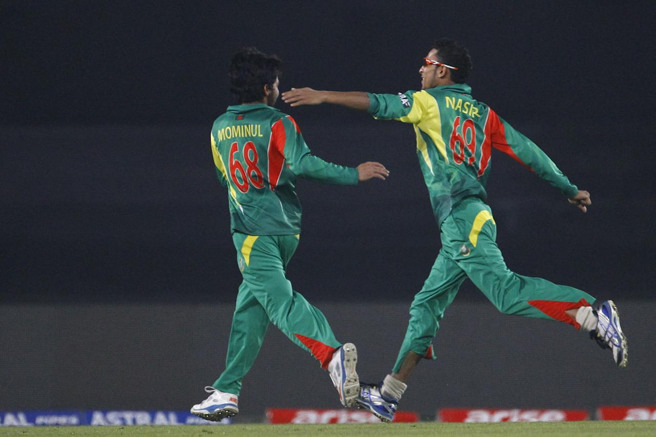 Bangladesh's Mominul Haque, left, celebrates with his teammate Nasir Hossain the wicket of Pakistan's Mohammad Hafeez during their match in the Asia Cup one-day international cricket tournament in Dhaka, Bangladesh, Tuesday, March 4, 2014. (AP Photo/A.M. Ahad)