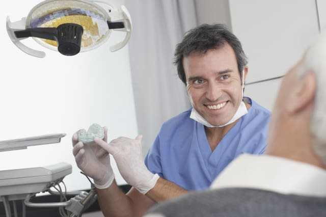 Dentist showing patient a mold of teeth and smiling