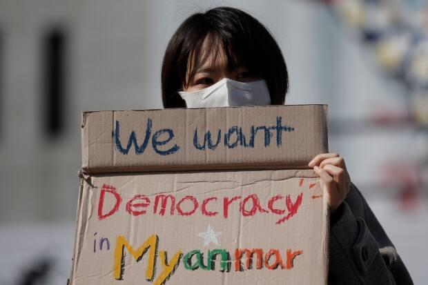 A member of a South Korean civic group holds a sign as she attends at a rally against Myanmar's military coup in Seoul, South Korea, Wednesday, March 3, 2021.