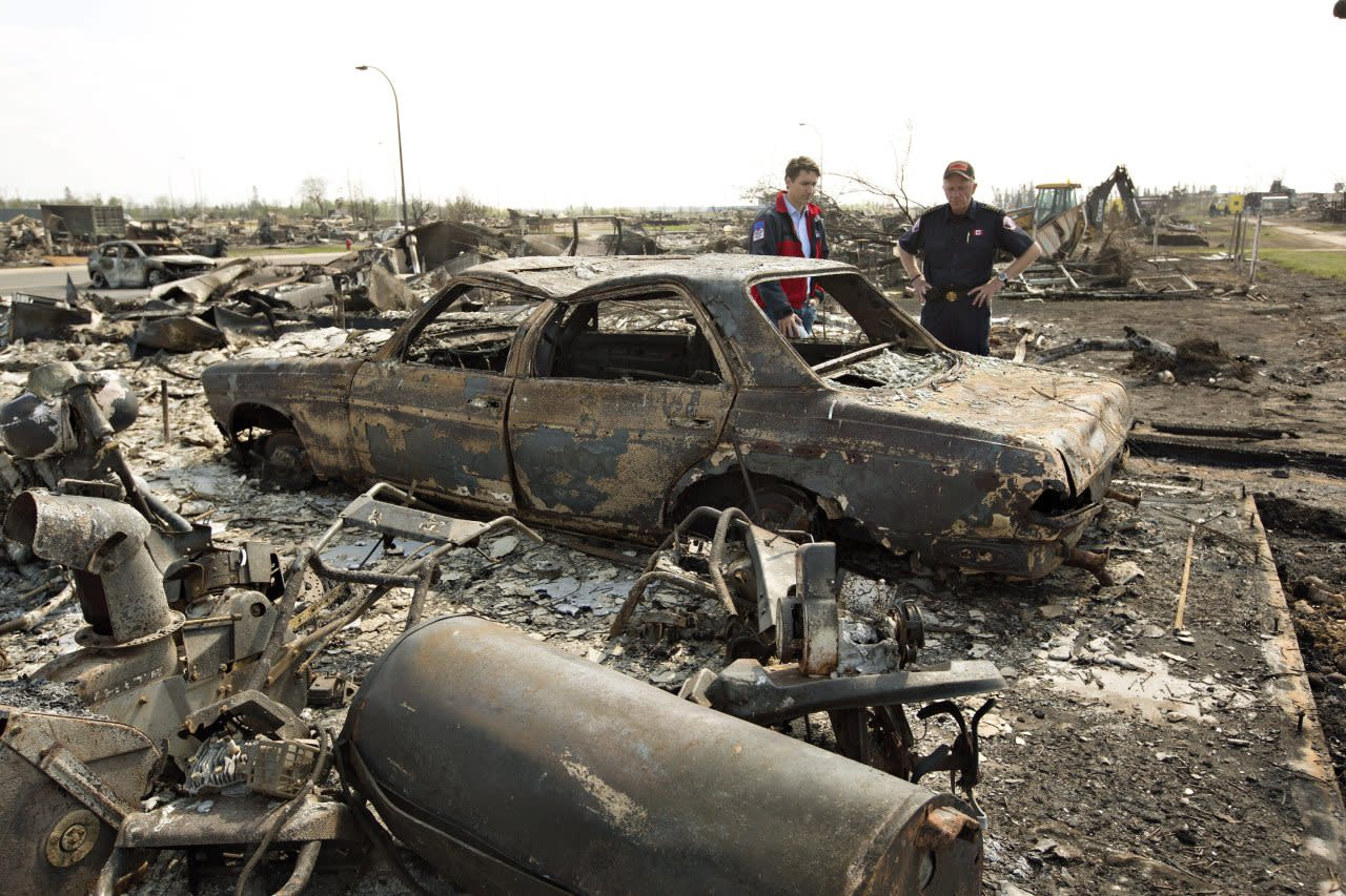 Prime Minister Justin Trudeau, left, and Fort McMurray Fire Chief Darby Allen look over a burnt out car during a visit to Fort McMurray, Alta., on Friday, May 13, 2016. THE CANADIAN PRESS/Jason Franson