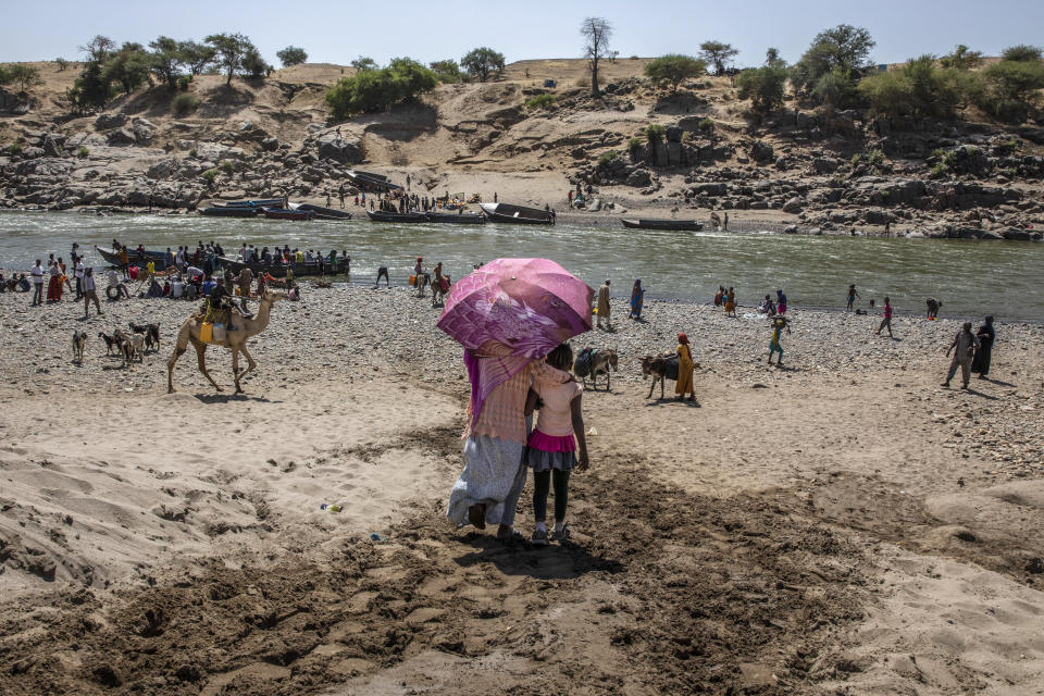 Refugees who fled the conflict in Ethiopia's Tigray region arrive on the banks of the Tekeze River on the Sudan-Ethiopia border, in Hamdayet, eastern Sudan, Saturday, Nov. 21, 2020. (AP Photo/Nariman El-Mofty)