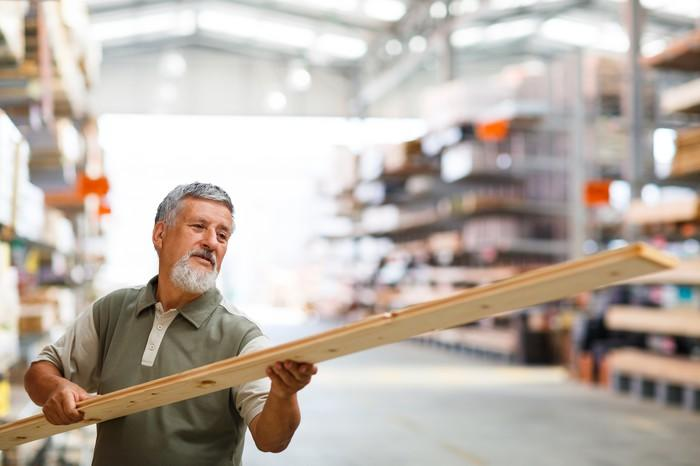 A man inspects a piece of lumber in a home improvement store