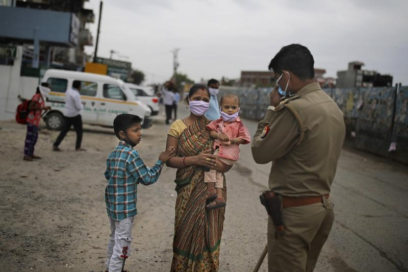 An Indian woman pleads in front of a policeman to let her pass a check point hoping to walk to their home with her family, a few hundred kms away, as the city comes under lockdown in Ghaziabad, on the outskirts of New Delhi, on Thursday, March 26, 2020. Some of India's legions of poor and people suddenly thrown out of work by a nationwide stay-at-home order began receiving aid distribution Thursday, as both the public and private sector work to blunt the impact of efforts to curb the coronavirus pandemic. Untold numbers of them are now out of work and many families have been left struggling to eat. (AP Photo/Altaf Qadri)