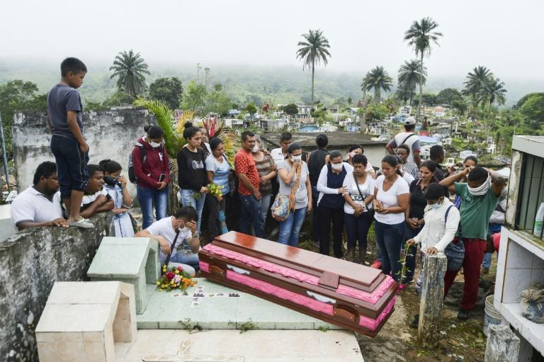 Relatives and friends of Deisy Rosero, 26, pray during her funeral at a cemetery in Mocoa, Putumayo department, southern Colombia on April 3, 2017
