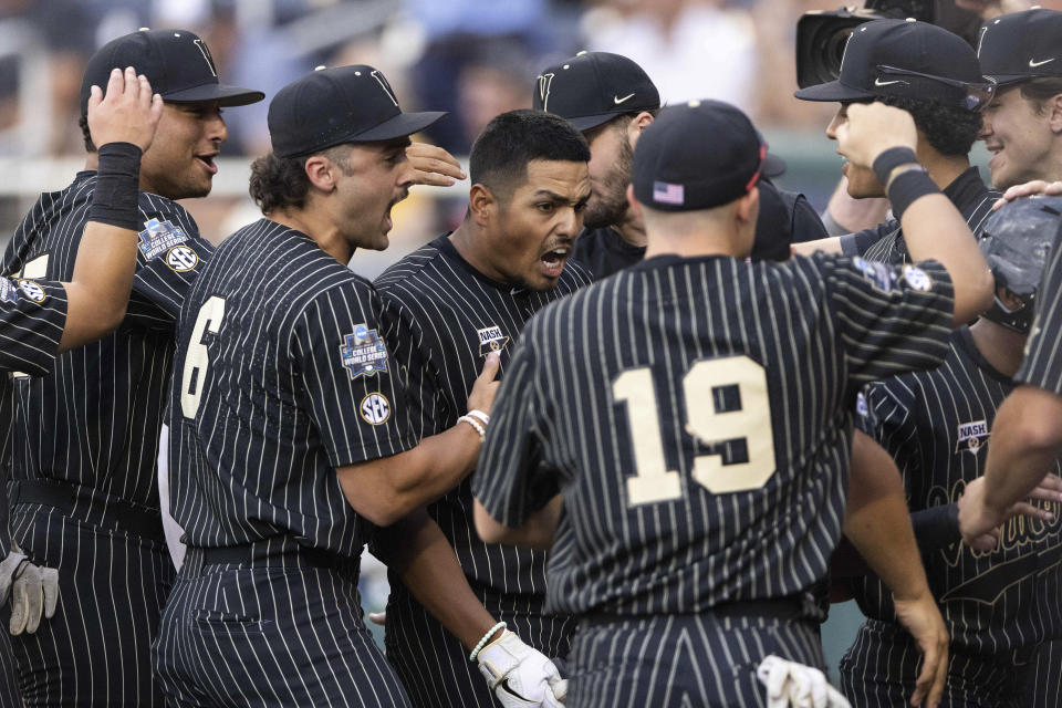 Vanderbilt's Jayson Gonzalez, center, celebrates with teammates as he returns to the dugout after hitting a two-run home run against Arizona in the fifth inning during a baseball game in the College World Series, Saturday, June 19, 2021, at TD Ameritrade Park in Omaha, Neb. (AP Photo/Rebecca S. Gratz)