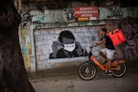A delivery man rides his bike past graffiti depicting Brazilian President Jair Bolsonaro in downtown Rio de Janeiro in March 2020