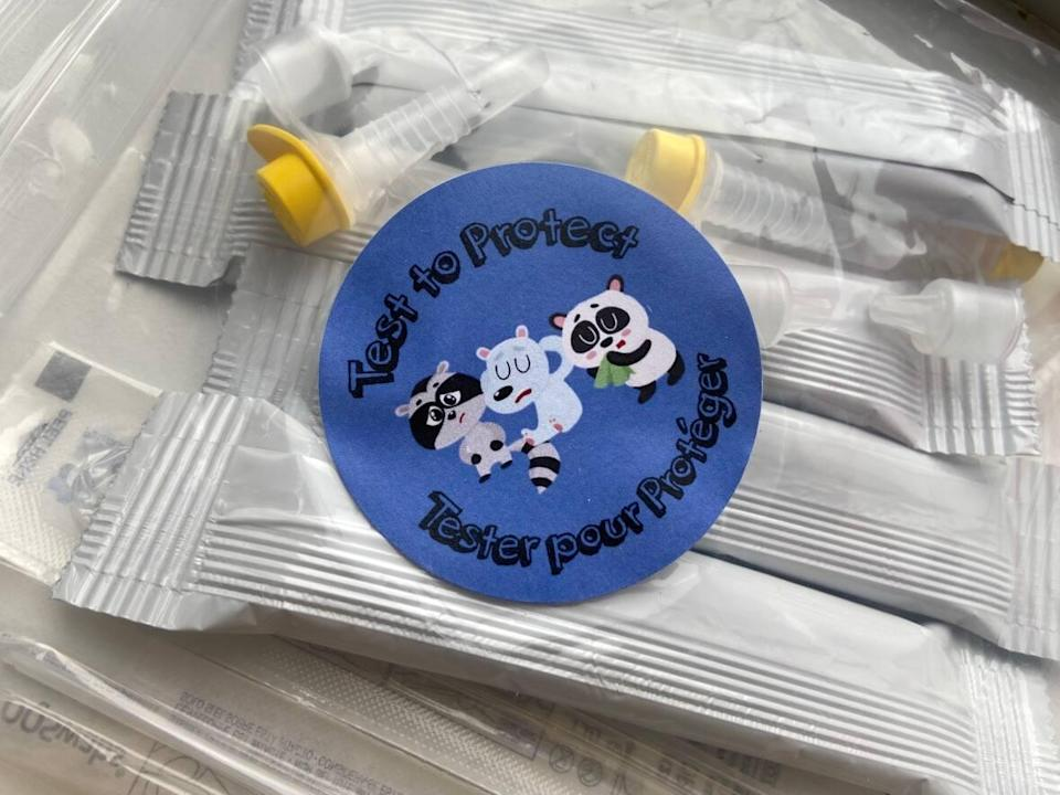 A sticker on a bag of COVID-19 rapid take-home tests encourages people to 'test to protect.' (Frances Willick/CBC - image credit)