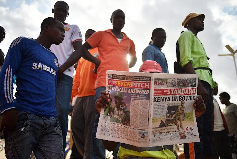 A man reads a newspaper in Garissa, Kenya, on April 3, 2015, with headlines and pictures concerning the attack a day earlier on the university there by Shebab fighters (AFP Photo/Carl de Souza)