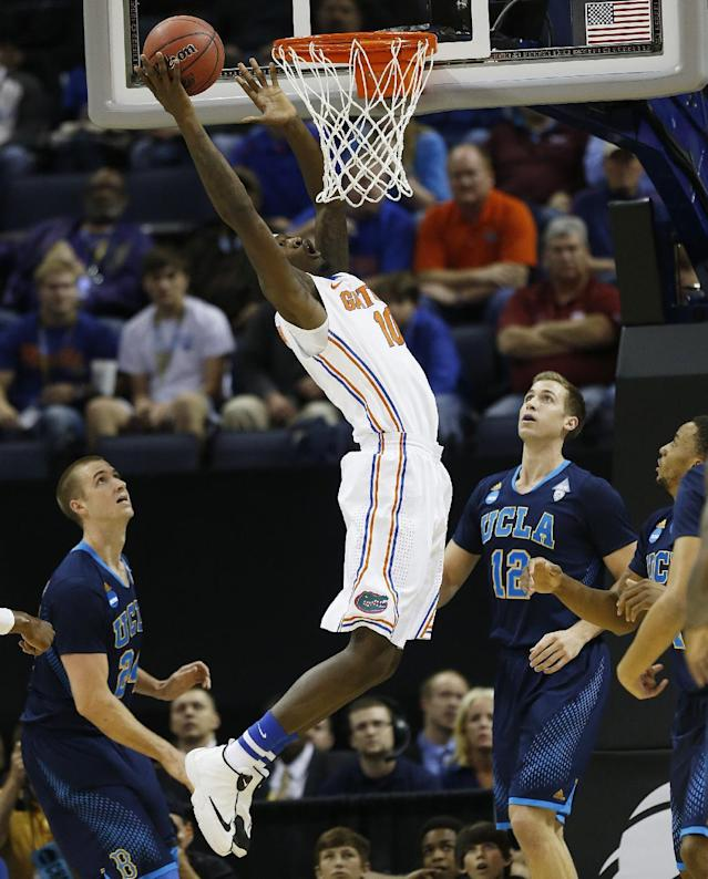 Florida forward Dorian Finney-Smith (10) shoots against UCLA forward Travis Wear (24) and UCLA forward David Wear (12) during the first half in a regional semifinal game at the NCAA college basketball tournament, Thursday, March 27, 2014, in Memphis, Tenn. (AP Photo/John Bazemore)