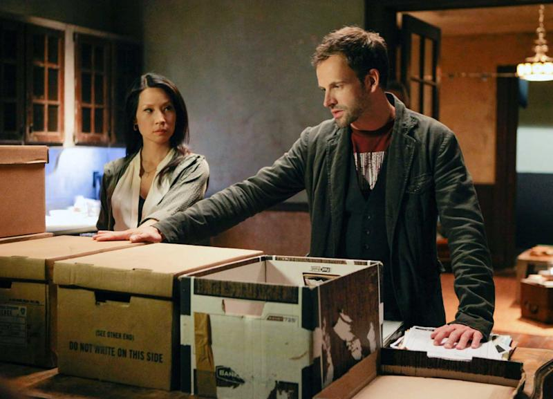 """This publicity image released by CBS shows Jonny Lee Miller, right, and Lucy Liu in a scene from the series, """"Elementary."""" (AP Photo/CBS, Giovanni Rufino)"""