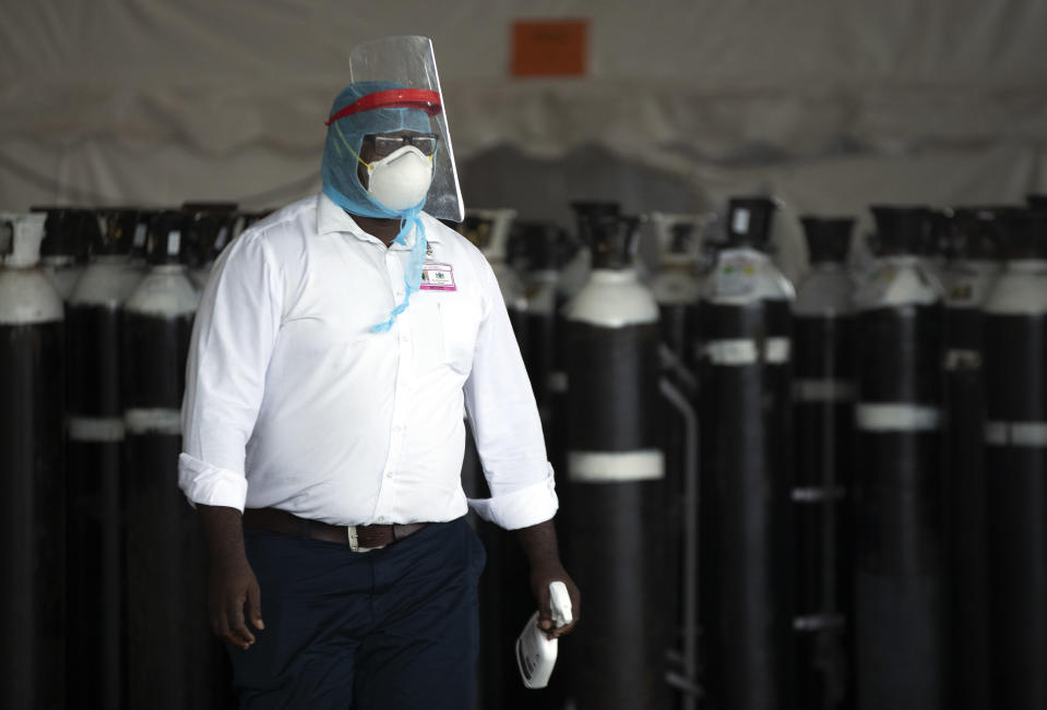 A health worker in a protective suit walks past oxygen cylinders at a makeshift emergency unit at Steve Biko Academic Hospital in Pretoria, South Africa, Monday, Jan. 11, 2021, which is battling an ever-increasing number of Covid-19 patients. (AP Photo/Themba Hadebe)