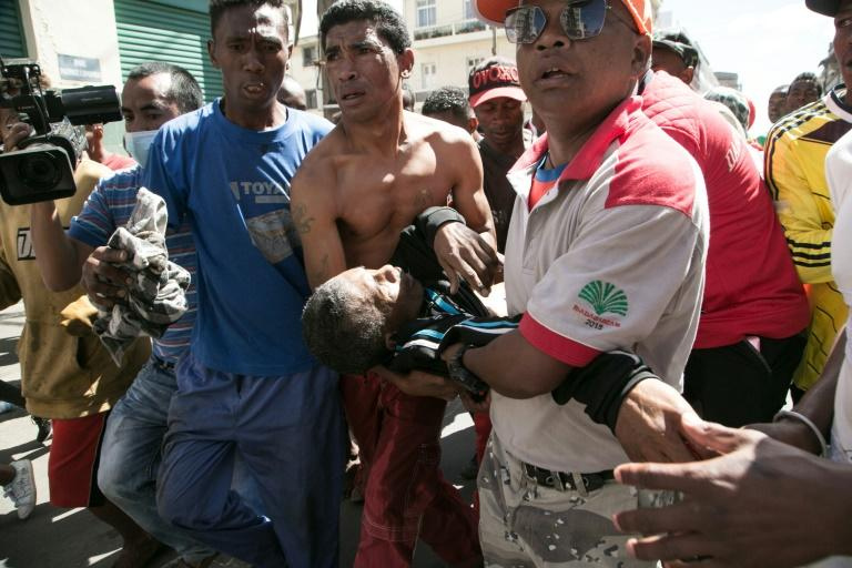 People carry a man shot in the abdomen during clashes with police at an opposition protest against new election laws in Madagascar