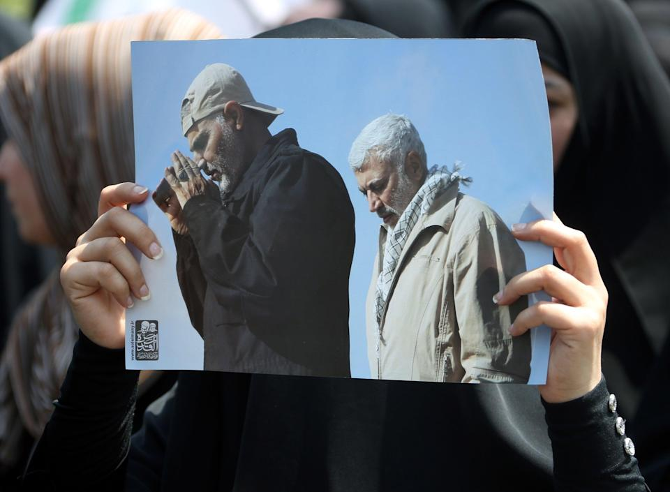 A supporter of Iran-backed Iraqi Shiite armed groups popular mobilisation forces carries the pictures of slain Abu Mahdi al-Muhandis and General Qassem Soleimani during a symbolic funeral (EPA)