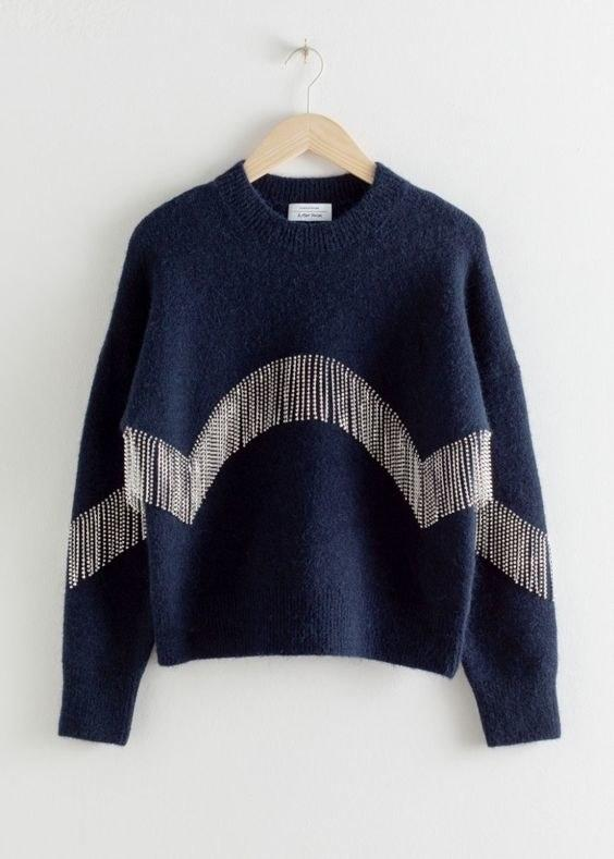 """$129, & Other Stories. <a href=""""https://www.stories.com/en_usd/clothing/knitwear/sweaters/product.diamant%C3%A9-fringe-sweater-blue.0774235001.html"""">Get it now!</a>"""