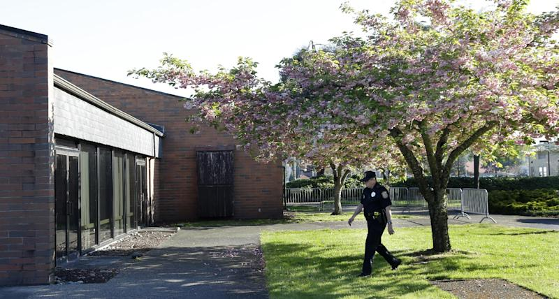 A U.S. Army civilian federal police officer patrols the perimeter of the building at Joint Base Lewis-McChord, Wash., where the court-martial for U.S. Army Sgt. John Russell began, Monday, May 6, 2013. Russell has already pleaded guilty to killing five fellow servicemen in Iraq in 2009, and and prosecutors are expected to argue that the killings were premeditated. (AP Photo/Ted S. Warren)