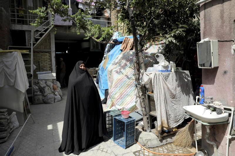 In this Saturday, July 6, 2019 photo, Zeinab Ebrahimi, 56, stands at the courtyard of her house which is under renovation, in the old District 12 of Tehran, Iran. Iran's large middle class has been hit hard by the fallout from unprecedented U.S. sanctions, including the collapse of the national currency. Perhaps most devastating has been the doubling of housing prices. The spike has uprooted tenants and made home ownership unattainable for most. (AP Photo/Ebrahim Noroozi)