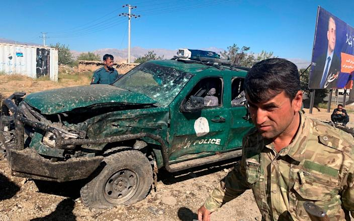 Afghan police inspect the site of the suicide attack in Parwan province - AP