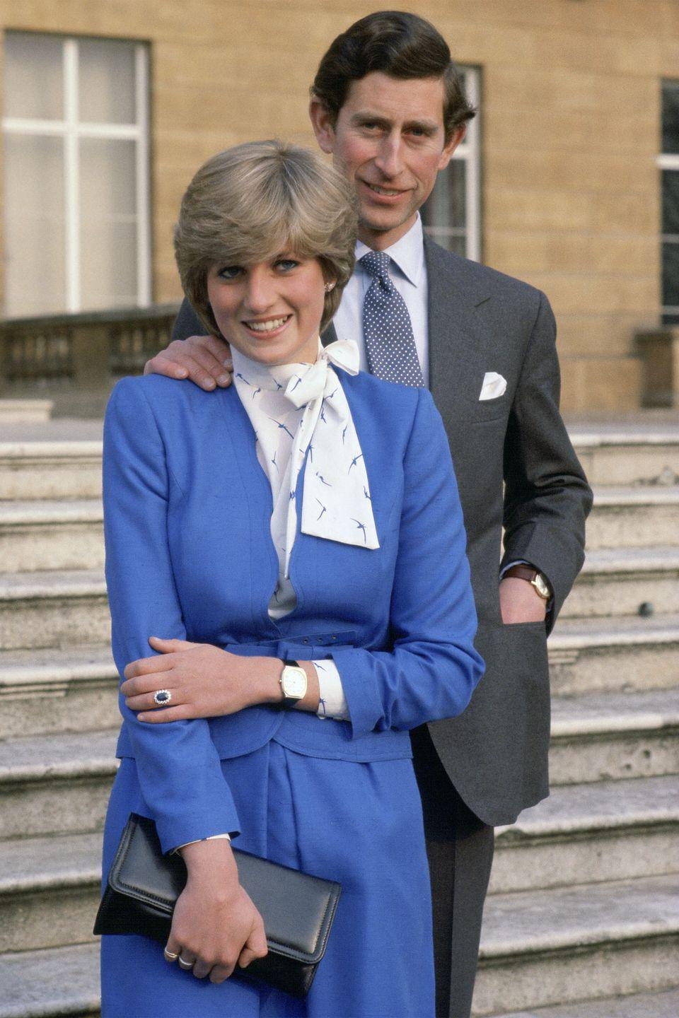 <p>In a royal blue skirt and blouse holding a black clutch at Buckingham Palace the day her engagement to Prince Charles was announced. </p>