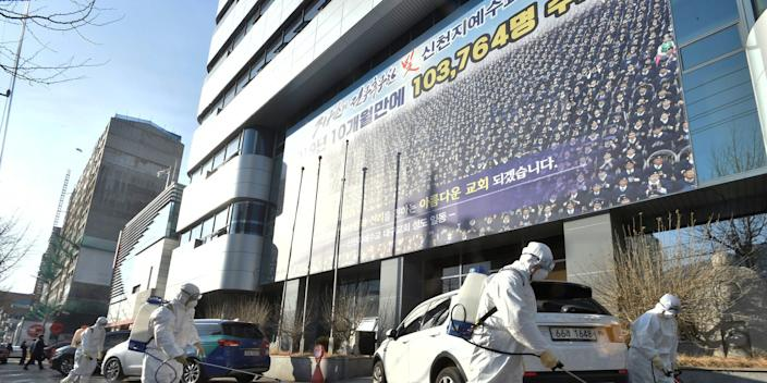 Workers sanitizing a street in front of a branch of the Shincheonji Church of Jesus the Temple of the Tabernacle of the Testimony in the South Korean city of Daegu.