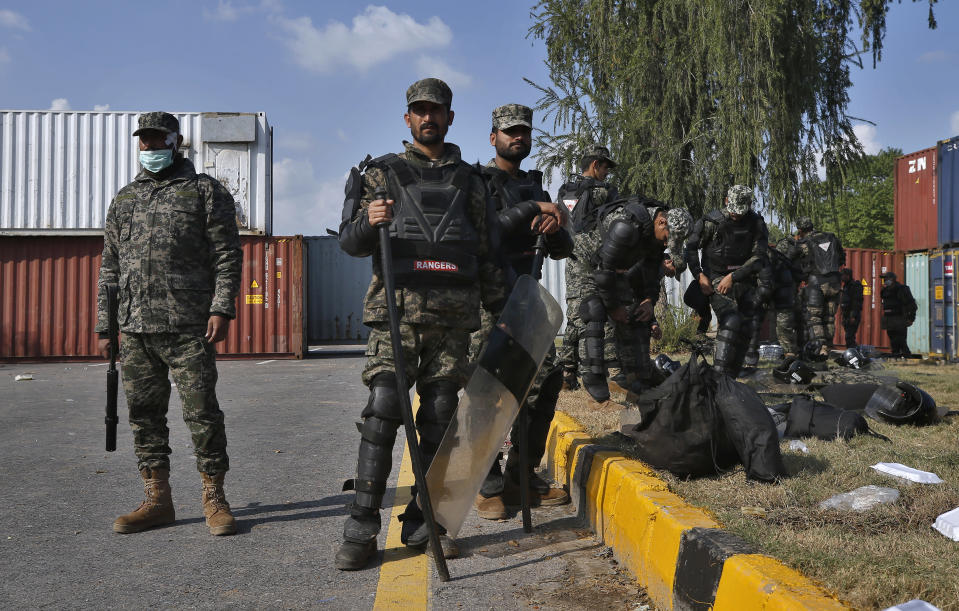 Paramilitary soldiers stand guard beside the shipping containers placed by authorities on a highway to stop supporters of 'Tehreek-e-Labaik Pakistan, a religious political party, entering into the capital during an anti-France rally in Islamabad, Pakistan, Monday, Nov. 16, 2020. The supporters are protesting the French President Emmanuel Macron over his recent statements and the republishing in France of caricatures of the Muslim Prophet Muhammad they deem blasphemous. (AP Photo/Anjum Naveed)