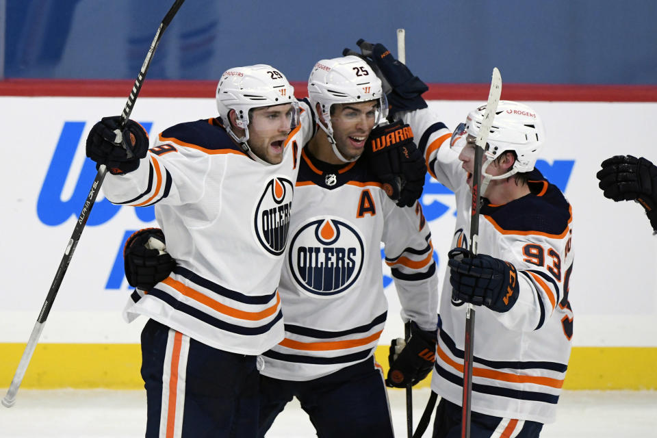 Edmonton Oilers' Leon Draisaitl (29) celebrates his game-winning goal with less than a second left against the Winnipeg Jets with teammates Darnell Nurse (25) and Ryan Nugent-Hopkins (93) in an NHL hockey game, Sunday, Jan. 24, 2021, in Winnipeg, Manitoba. (Fred Greenslade/The Canadian Press via AP)