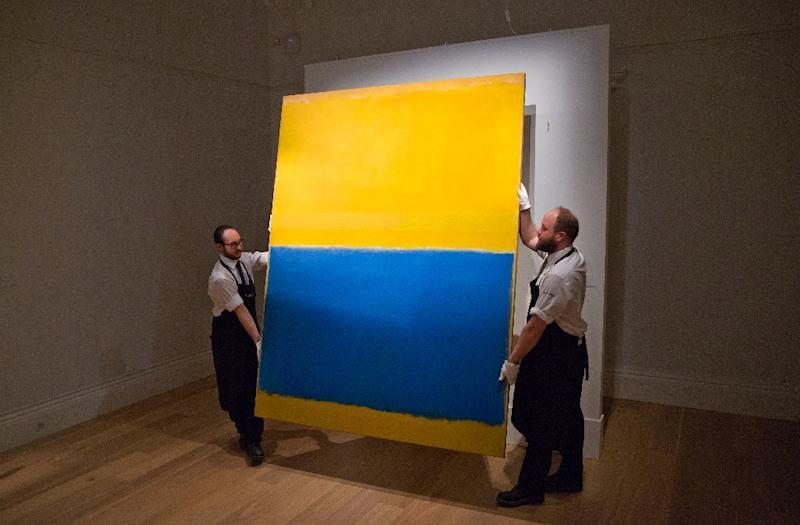 """Employees of Sotheby's auction house pose with US artist Mark Rothko's """"Untitled (Yellow and Blue)"""" painted in 1954 which sold for $46.5 million at a Sotheby's auction in New York"""