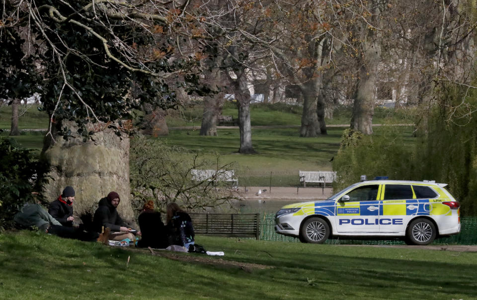 """People observe coronavirus guidelines as a police car patrols nearby in central London, Monday, April 5, 2021. The British government says all asymptomatic people in England will be able to get two free coronavirus tests per week, starting Friday, as a way to stamp out new outbreaks, and Prime Minister Boris Johnson said that regular testing would help """"stop outbreaks in their tracks.""""(AP Photo/Frank Augstein)"""