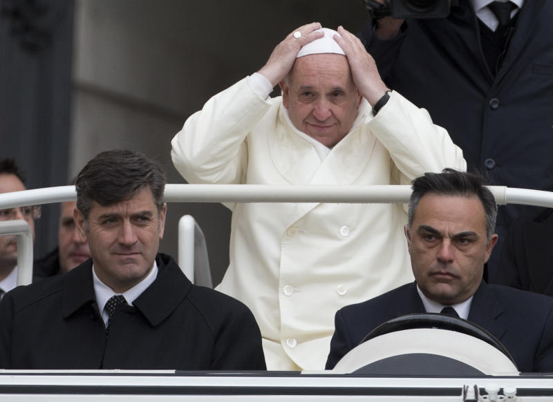 Pope Francis adjusts his skull cap as he arrives on his pope-mobile for his weekly general audience in St. Peter's Square at the Vatican, Wednesday, Nov. 27, 2013. Francis is bundling up for the cold snap belting Italy, donning a white double-breasted winter coat and scarf for his weekly general audience. (AP Photo/Alessandra Tarantino)