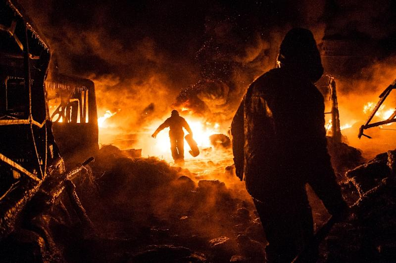 Ukrainian protesters walk past a burning barricade during the 2014 clashes that forced the overthrow of pro-Russian president Viktor Yanukovych (AFP Photo/Volodymyr Shuvayev)