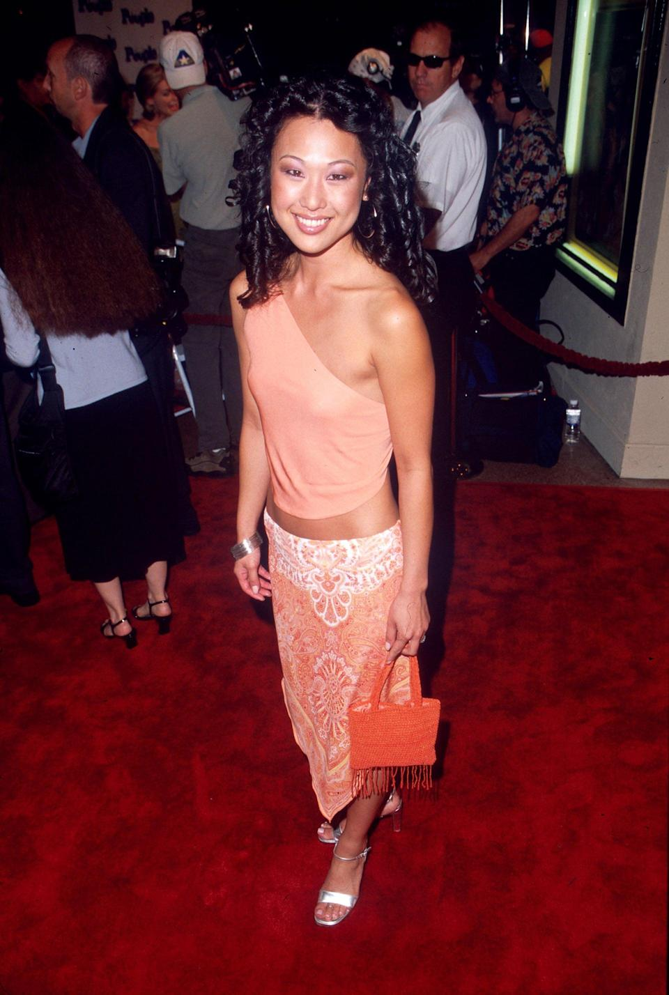 """<p>""""W-w-w-whitney!"""" Nicole's low-slung skirt and one-shoulder top were peach-perfect, and she played up the palette with a bolder-toned beaded fringe bag. Look closely, and you can make out a toe ring that dazzled alongside Nicole's metallic sandals.</p>"""