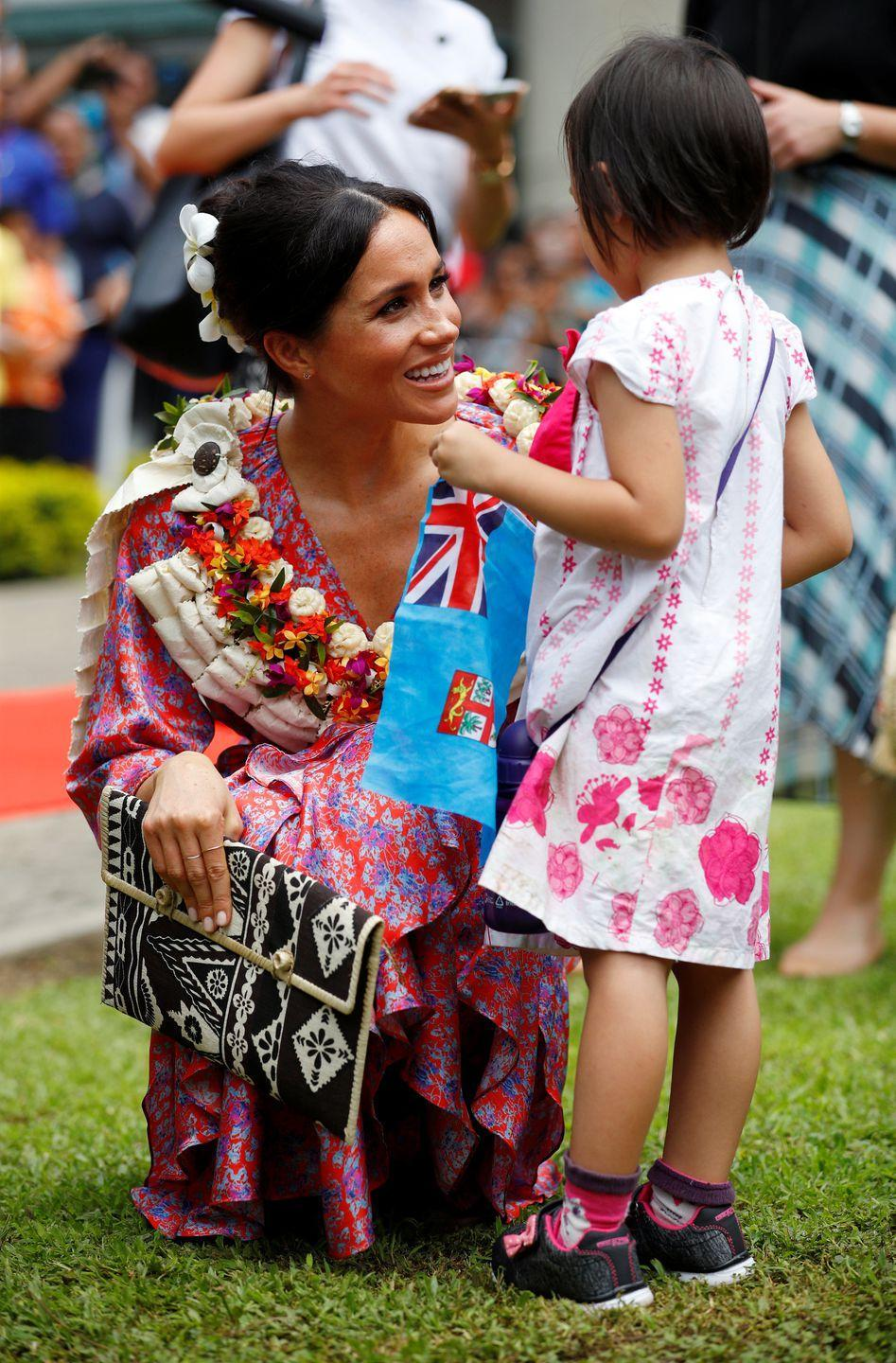 <p>Wearing a beautiful, bright pom-pom dress and flowers in her hair, Meghan chatted to a little girl holding a Fijian flag in Suva.</p>