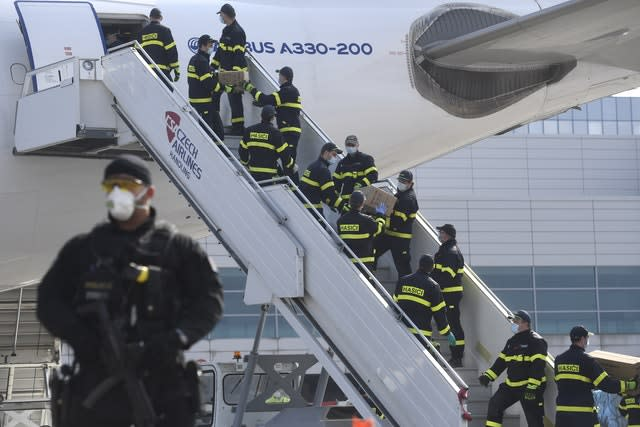Firefighters unload a plane in Prague