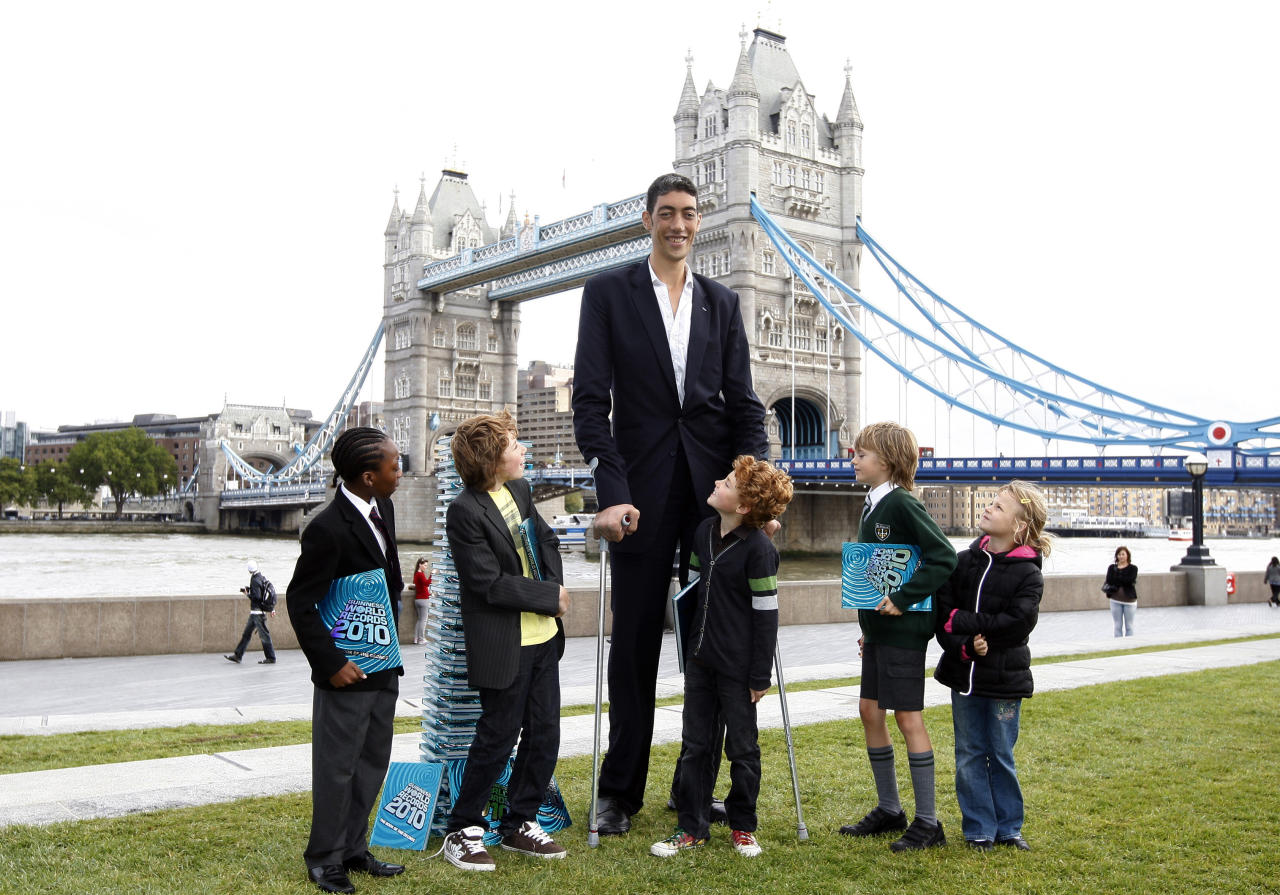 The world's tallest man, Sultan Kosen from Turkey, poses for photographers next to school children at an event in London September 16, 2009. Kosen, who is 2 metres 46.5 cm (8 feet 1 inch) tall and also claims the record for the largest hands and largest feet, attended the event to promote the Guinness World Records 2010 book. REUTERS/Andrew Winning (BRITAIN SOCIETY IMAGES OF THE DAY)