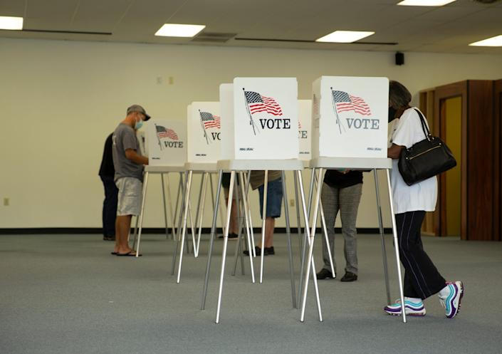 Voters cast ballots in the general election, Friday, Sept. 18, 2020, at the Office of Elections satellite location in Spotsylvania, Va., on the first day of the state's 45-day early voting period.
