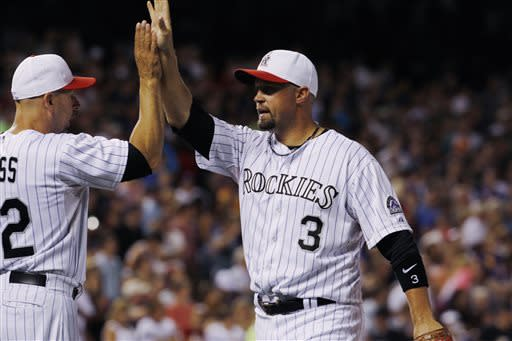 Colorado Rockies manager Walt Weiss, left, congratulates right fielder Michael Cuddyer after he lead the Rockies to 9-5 victory over the Los Angeles Dodgers in a baseball game in Denver on Thursday, July 4, 2013. (AP Photo/David Zalubowski)