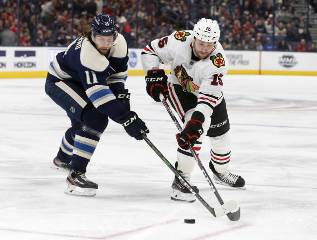Columbus Blue Jackets forward Kevin Stenlund, left, of Sweden, and Chicago Blackhawks forward Zack Smith chase the puck during the second period of an NHL hockey game in Columbus, Ohio, Sunday, Dec. 29, 2019. (AP Photo/Paul Vernon)
